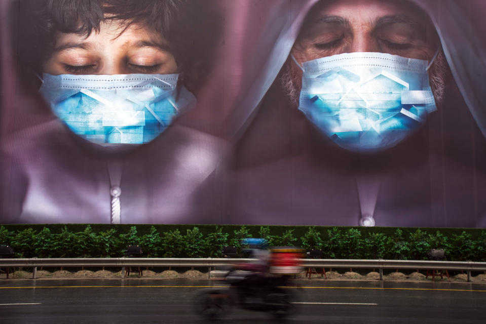 A motorcycle deliveryman rides past a billboard urging people to stay during the coronavirus pandemic in Dubai, United Arab Emirates, Wednesday, April 15, 2020. (AP Photo/Jon Gambrell)