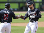 Atlanta Braves Ender Inciarte, right, gets five from first base coach Eric Young, left, after hitting a single against the Minnesota Twins during the third inning of an MLB spring training game Tuesday, March 2, 2021, in North Port, Fla. (Curtis Compton/Atlanta Journal-Constitution via AP)