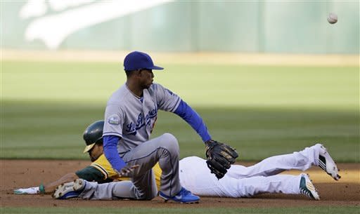 Oakland Athletics' Coco Crisp, rear, slides safely into second base for a double as Los Angeles Dodgers shortstop Dee Gordon looks for the ball during the first inning of their baseball game in Oakland, Calif., Tuesday, June 19, 2012. (AP Photo/Eric Risberg)