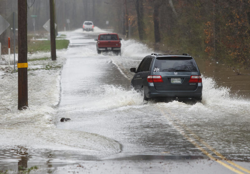 Vehicles travel through floodwaters on Boy Scout Road on Saturday, Feb. 23, 2019, in Soddy-Daisy, Tenn. Area emergency agencies are warning motorists not to attempt to drive through flooded roads. A week of rainfall led to widespread flooding across the Tennessee Valley. (Doug Strickland/Chattanooga Times Free Press via AP)