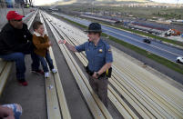 """Colorado State Patrol Trooper Josh Lewis fist bumps 3-year-old Lincoln Delagarza, of Northglenn, Colorado, before racing begins at Bandimere Speedway west of Denver on May 5, 2021. The State Patrol runs a program called """"Take it to the Track"""" in hopes of luring racers away from public areas to a safer and more controlled environment, even allowing participants to race a trooper driving a patrol car. The program's goals have gained new importance and urgency this year as illegal street racing has increased amid the coronavirus pandemic. (AP Photo/Thomas Peipert)"""
