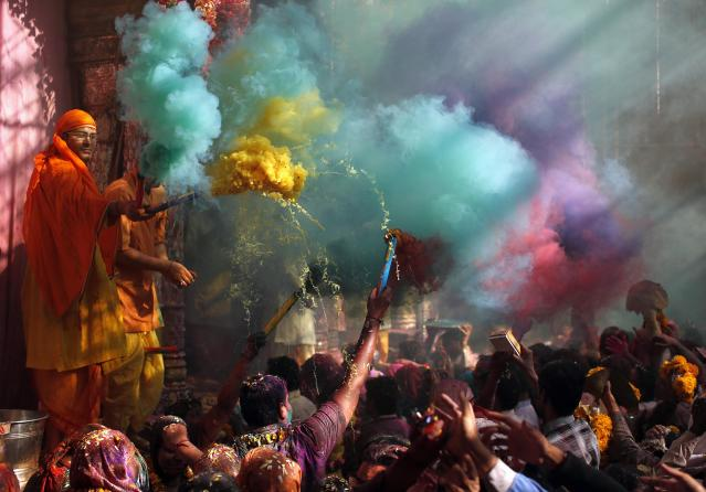 Hindu priests throws coloured powder at the devotees during Holi celebrations at Bankey Bihari temple in Vrindavan, in the northern Indian state of Uttar Pradesh, March 13, 2014. Holi, also known as the Festival of Colours, heralds the beginning of spring and is celebrated all over India. REUTERS/Ahmad Masood (INDIA - Tags: SOCIETY RELIGION TPX IMAGES OF THE DAY)
