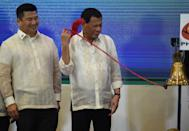 Philippine President Rodrigo Duterte (R) rings the bell at the Philippine Stock Exchange in the financial district of Makati, suburban Manila on July 11, 2017, coinciding with the tenth anniversary of the listing of petroleum company Phoenix as the company's president and CEO Dennis Uy looks on. / AFP PHOTO / TED ALJIBE (Photo credit should read TED ALJIBE/AFP via Getty Images)