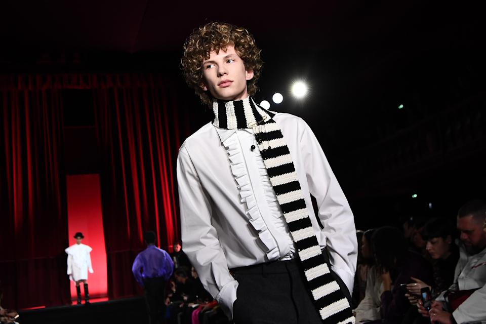 The AMI by Alexandre Mattiussi man adds a bold touch to his discreetly romantic jabot shirt by throwing a striped scarf into the mix. Paris, January 14, 2020.