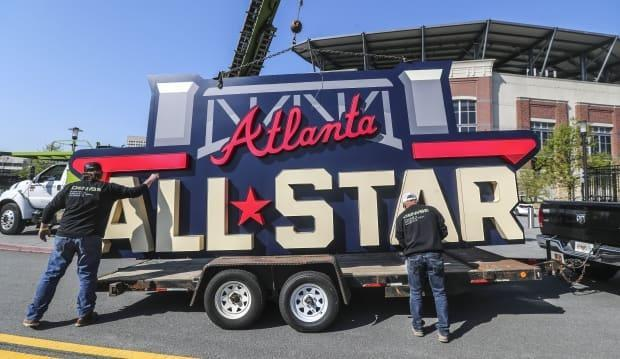 Workers load an All-Star sign onto a trailer after it was removed from Truist Park in Atlanta in April after MLB announced it would relocate the game to Denver.
