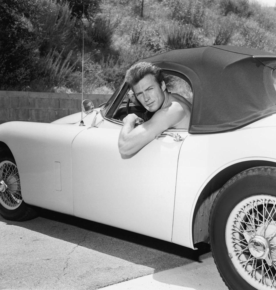 <p>Clint Eastwood leaning out the window of a Jaguar convertible. </p>