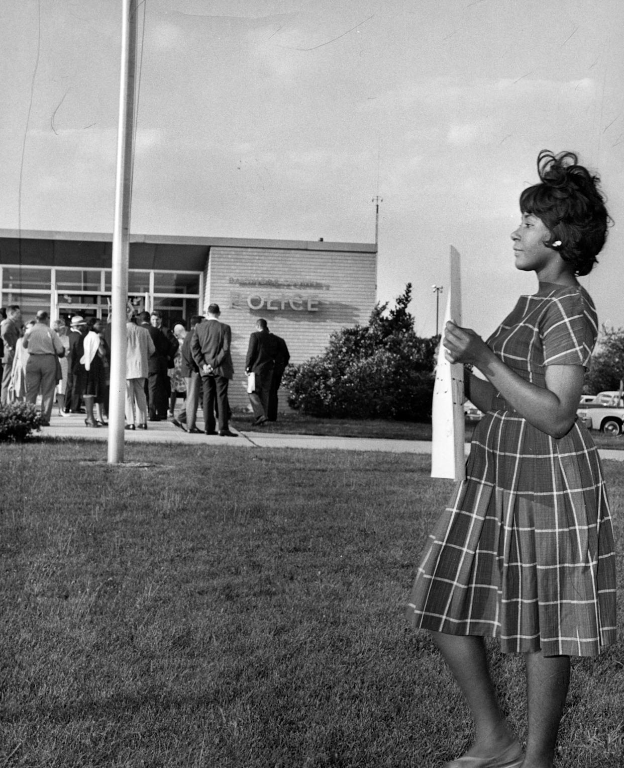 A full length portrait of a woman holding up a poster and demonstrating outside a Police Station, Gwynn Oak, Maryland, July 1, 1963.