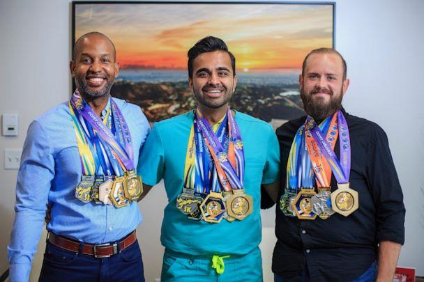 PHOTO: Christopher Hasty, right, poses with friends who completed the 'Dopey Challenge' alongside him wearing all four medals. (Courtesy Christopher Hasty)