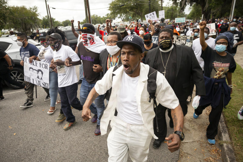 Malik Muhammad, center, joins a group of people marching from the Glynn County Courthouse in downtown to a police station after a rally to protest the shooting of Ahmaud Arbery, Saturday, May 16, 2020, in Brunswick, Ga. (AP Photo/Stephen B. Morton)
