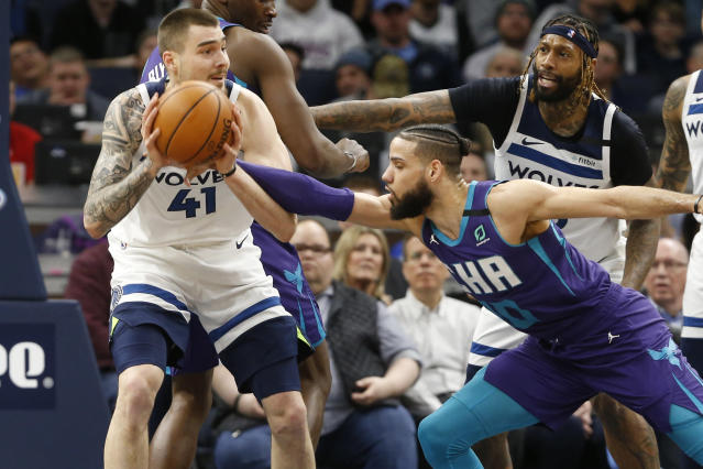 Charlotte Hornets' Caleb Martin, right, tries to knock the ball away from Minnesota Timberwolves' Juancho Hernangomez during the first half of an NBA basketball game Wednesday, Feb. 12, 2020, in Minneapolis. (AP Photo/Jim Mone)