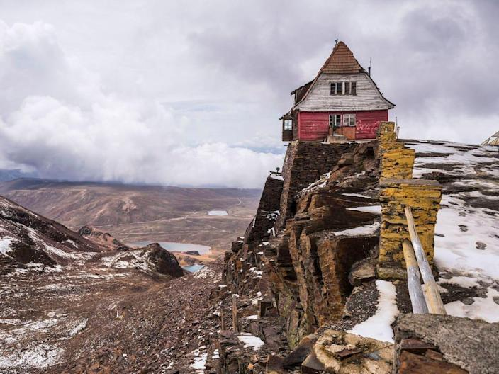 An abandoned ski resort building sits on the cliffside of the Chacaltaya mountain.