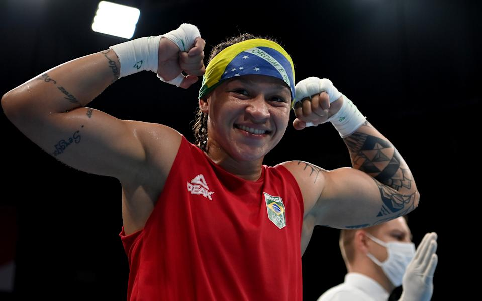 TOKYO, JAPAN - AUGUST 03: Beatriz Ferreira (red) of Team Brazil celebrates victory over Raykhona Kodirova of Team Uzbekistan during the Women's Light (57-60kg) quarter final on day eleven of the Tokyo 2020 Olympic Games at Kokugikan Arena on August 03, 2021 in Tokyo, Japan. (Photo by Luis Robayo - Pool/Getty Images)