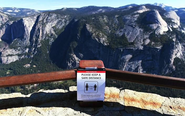 A reminder to keep social distancing can be seen at Glacier Point overlooking Yosemite Valley as the park reopens after closure due to coronavirus Thursday morning, June 11, 2020.