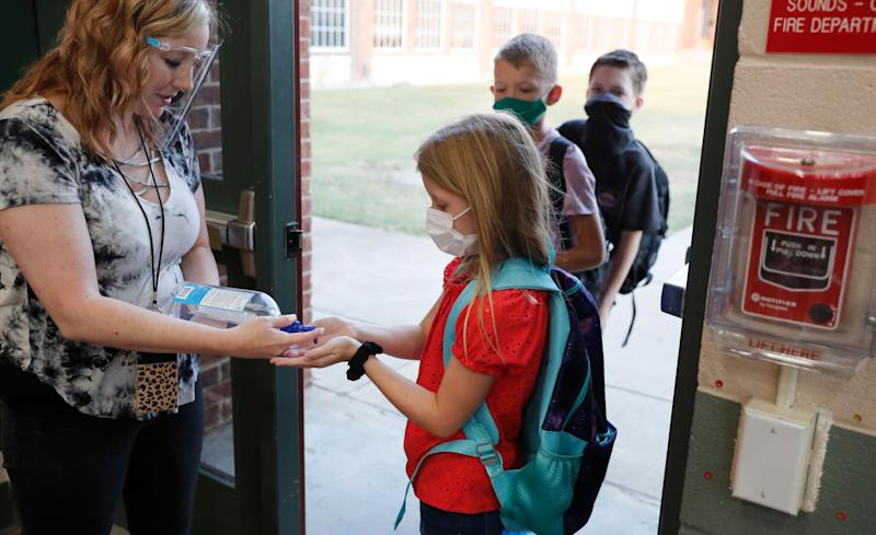 Wearing masks to prevent the spread of COVID-19, elementary school students use hand sanitizer before entering their classroom in Godley, Texas, on Wednesday. Schools across the country have grappled with the issue of whether to resume in-person classes or conduct them online amid the pandemic. (Photo: ASSOCIATED PRESS)