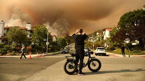 PHOTO: A man takes a photo of the plume of smoke created by the Palisades fire in Topanga State Park, North West of Los Angeles, May 15, 2021. (Patrick T. Fallon/AFP via Getty Images)