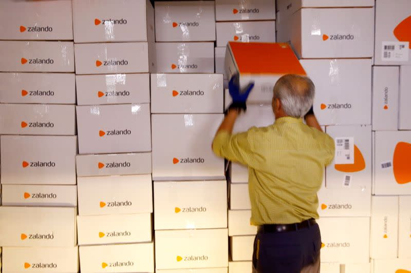 FILE PHOTO: An employee unloads parcel of online mail order company Zalando from a container at the parcel distribution center of Swiss Post in Frauenfeld