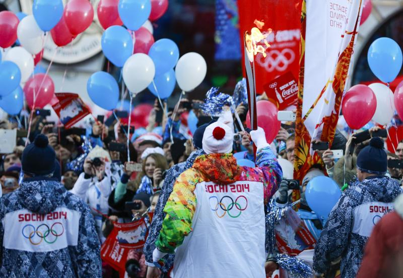 Alexey Voyevoda, a former Olympic bobsledder, who won silver in the 4-man bobsled in Turin in 2006, carries the Olympic torch as it makes it's way throughout the streets of the Rosa Khutor ski resort in Krasnaya Polyana, Russia at the Sochi 2014 Winter Olympics, Wednesday, Feb. 5, 2014. (AP Photo/Gero Breloer)