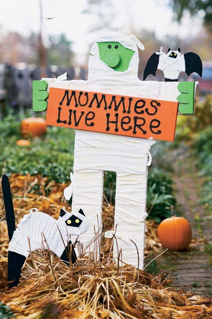 """<p>This adorable DIY mummy sign doesn't just look cute — it also glows in the dark. </p><p><strong><em><a href=""""https://www.womansday.com/home/crafts-projects/a90/mummy-sign/"""" rel=""""nofollow noopener"""" target=""""_blank"""" data-ylk=""""slk:Get the Mummy Yard Sign tutorial"""" class=""""link rapid-noclick-resp"""">Get the Mummy Yard Sign tutorial</a>.</em></strong></p><p><a class=""""link rapid-noclick-resp"""" href=""""https://www.amazon.com/neon-nights-Black-Paints-Fluorescent/dp/B009EZXX6U?tag=syn-yahoo-20&ascsubtag=%5Bartid%7C10070.g.2488%5Bsrc%7Cyahoo-us"""" rel=""""nofollow noopener"""" target=""""_blank"""" data-ylk=""""slk:SHOP GLOW-IN-THE-DARK PAINT"""">SHOP GLOW-IN-THE-DARK PAINT</a></p>"""