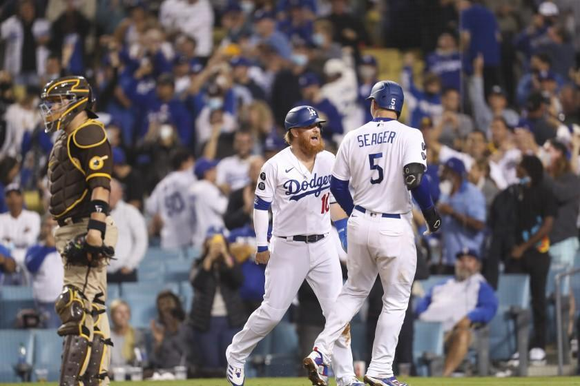Los Angeles, CA - September 29: Padres catcher Victor Caratini, left, looks away as Dodgers Justin Turner left, and Corey Seager celebrate Seager's game-winning two-run home run in the bottom of the eighth inning against the San Diego Padres at Dodger Stadium in Los Angeles on Wednesday, Sept. 29, 2021. Dogers won 11-9. (Allen J. Schaben / Los Angeles Times)