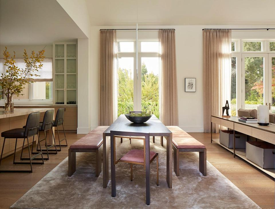 In between the kitchen and living room, a Marmol Radziner custom Glencoe dining table is surrounded by Marmol Radziner Glencoe dining benches and Stephen Kenn Inheritance dining chairs, both upholstered with Spinneybeck Ducale Velour leather.