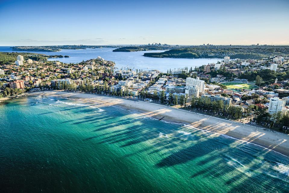 """<p><strong>Give us the wide-angle view: what kind of beach are we talking about?</strong><br> One of Sydney's most famous surf spots, Manly Beach is a huge sweep of golden sand backed by pretty pine trees. It's actually three beaches in one—South Steyne, North Steyne, and surf-friendly Queenscliff, stretching almost two kilometers—and is the first of the city's Northern Beaches which run from here up to Palm Beach.</p> <p><strong>Lovely. How accessible is it?</strong><br> Taking the iconic half-hour Manly Ferry from Circular Quay to Manly Wharf is half the fun, with fantastic views of the <a href=""""https://www.cntraveler.com/activities/sydney/sydney-harbour-bridge?mbid=synd_yahoo_rss"""" rel=""""nofollow noopener"""" target=""""_blank"""" data-ylk=""""slk:Sydney Harbour Bridge"""" class=""""link rapid-noclick-resp"""">Sydney Harbour Bridge</a>, <a href=""""https://www.cntraveler.com/activities/sydney/sydney-opera-house?mbid=synd_yahoo_rss"""" rel=""""nofollow noopener"""" target=""""_blank"""" data-ylk=""""slk:Sydney Opera House"""" class=""""link rapid-noclick-resp"""">Sydney Opera House</a> and city skyline (especially if you bag a seat outside). Privately-operated Manly Fast Ferry journeys, lasting 19 minutes, cost more. On arrival, you'll spy family-friendly harbor beaches on both sides of the wharf offering sheltered swimming. For proper waves though, follow the crowd along short pedestrian street The Corso across the peninsula to oceanfront Manly Beach.</p> <p><strong>Got it. Decent services and facilities, would you say?</strong><br> A promenade links the trio of ocean beaches dotted with changing rooms. Manly is stuffed with surf shops selling boards, flippers, masks and snorkels, with gear for rent too (fashion and homewares stores also get a look in). Need to refuel? Try Fika Swedish Kitchen (5b Market Lane) or Showbox Coffee Brewers (19 Whistler Street). At Manly Wharf, Hugo's Manly serves wood-fired pizza and wine or kick back at Manly Wharf Hotel for casual food and drinks – both offer outdoor tables. Microbre"""