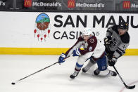Colorado Avalanche defenseman Cale Makar (8) reaches for the puck next to Los Angeles Kings left wing Brendan Lemieux (48) during the first period of an NHL hockey game Saturday, May 8, 2021, in Los Angeles. (AP Photo/Marcio Jose Sanchez)