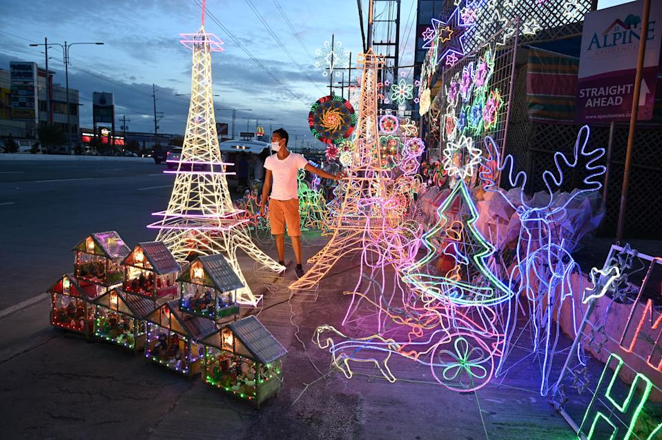 FILE PHOTO: This photo taken on October 6, 2020 shows a worker standing beside lanterns and lit ornaments, including several shaped in the likeness of the Eiffel Tower, for sale during the festive season at a shop in San Fernando town in Pampanga province. (Photo: TED ALJIBE/AFP via Getty Images)