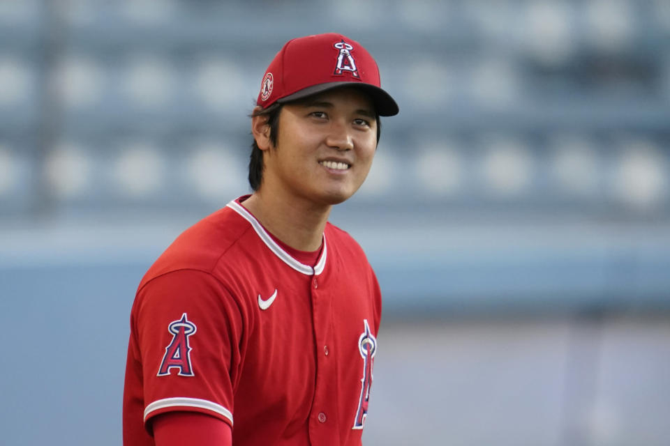 Los Angeles Angels starting pitcher Shohei Ohtani smiles as he warms up before a spring training exhibition baseball game against the Los Angeles Dodgers, Monday, March 29, 2021, in Los Angeles. (AP Photo/Marcio Jose Sanchez)