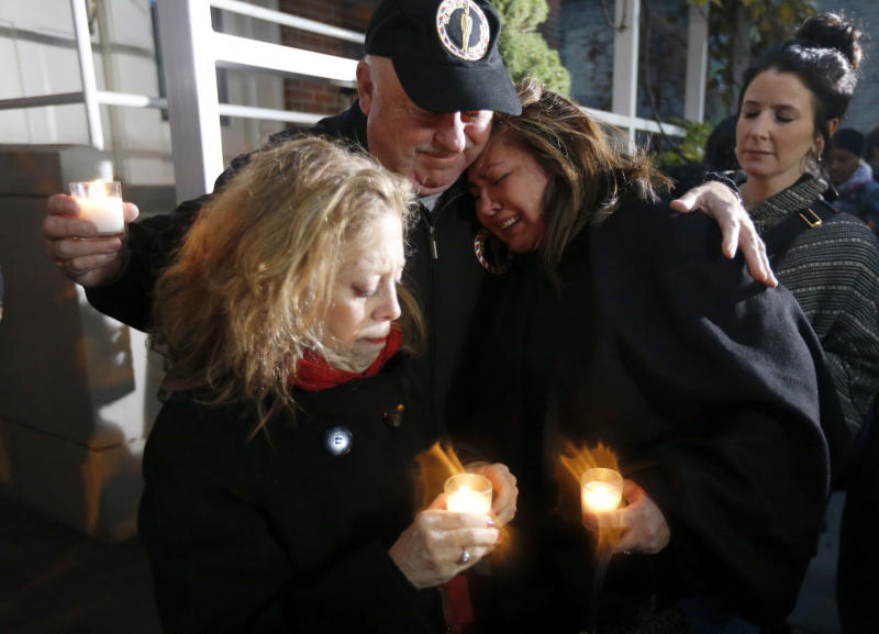 Chef John Kaufmann, center, consoles Chef Priscila Satkoff, right, and Jamie Pellar, left, during a candlelight memorial for Chicago Chef Charlie Trotter outside his former restaurant Tuesday, Nov. 5, 2013, in Chicago. Trotter, 54, died Tuesday, a year after closing his namesake Chicago restaurant that was credited with putting his city at the vanguard of the food world and training dozens of the nation's top chefs, including Grant Achatz and Graham Elliot. (AP Photo/Charles Rex Arbogast)