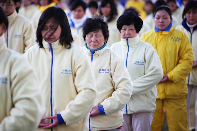 SYDNEY, AUSTRALIA - JULY 21: Falun Gong Practitioners meditate on the 14th anniversary of the beginning of the persecution of Falun Gong in China on July 21, 2013 in Sydney, Australia. In July of 1999, the communist Chinese government outlawed the spiritual practise of Falun Gong, declaring it illegal and forbidding citizens to practise. Followers believe thousands of practitioners have been killed, imprisoned or put in labour camps in China since 1999. (Photo by Brendon Thorne/Getty Images)