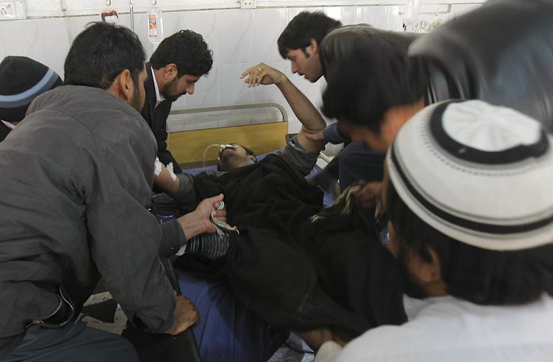 Hospital staff members help an injured health move to another room at a local hospital in Peshawar, Pakistan, Saturday, Dec. 28, 2013. Pakistani police said that gunmen attacked an anti-polio vaccination center in Pakistan's northwest and killed at least one medic on duty, then fled the scene. (AP Photo/Mohammad Sajjad)