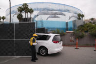 A minivan enters the loading dock area of the Long Beach Convention Center, in Long Beach, Calif., Thursday, April 22, 2021, where migrant children found at the U.S.-Mexico border without a parent will be temporarily housed. The beds are in pods of 30. The center is able to house up to 1,000 children and the first children are expected to arrive Thursday afternoon. (AP Photo/Jae C. Hong)
