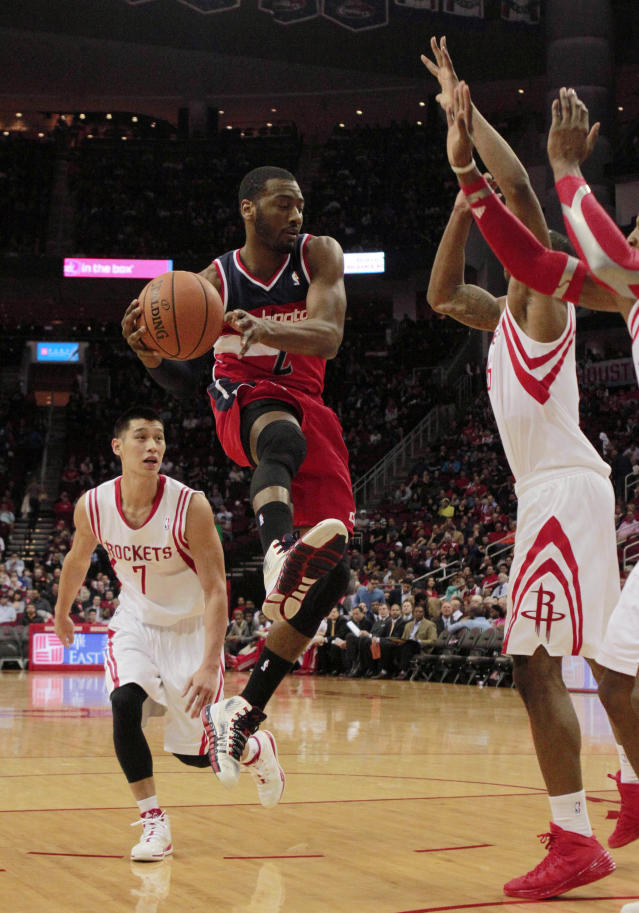 Washington Wizards guard John Wall (2) goes up to shoot followed by Houston Rockets guard Jeremy Lin (7) during the first half of an NBA basketball game in Houston, Wednesday, Feb. 12, 2014. (AP Photo/Richard Carson)