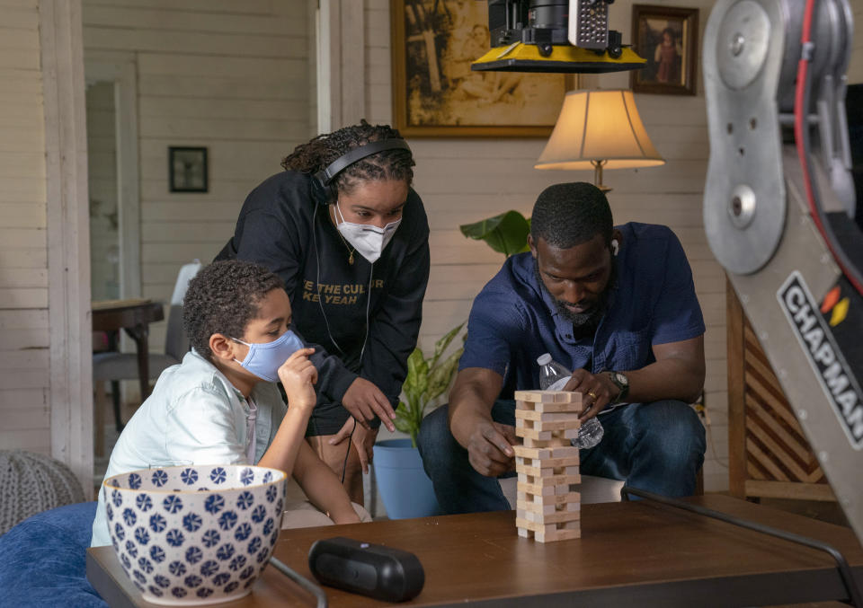 "This image released by Warner Bros. Entertainment shows director Cierra Glaude, center, with Kofi Siriboe, right, and Ethan Hutchison as they set up a scene for ""Queen Sugar."" When the series debuted in 2016, Glaude worked as a production assistant on the show. Five years later, she's been promoted to director for season five on the Oprah Winfrey Network series. (Skip Bolen/2020 Warner Bros. Entertainment via AP)"