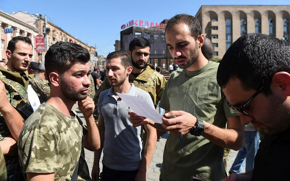 People attend a meeting to recruit military volunteers after Armenian authorities declared martial law and mobilised its male population following clashes with Azerbaijan - MELIK BAGHDASARYAN/REUTERS