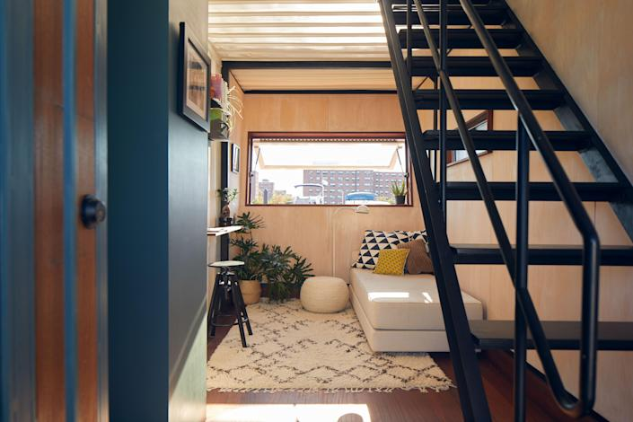 "The couple describes the space as an ""upside-down house. The bedroom, bathroom, and living area are downstairs, and the kitchen and entertaining space are upstairs."" The interior walls are clad in humidity-tolerant maple plywood, and the seams were left exposed adding to the modern appeal. The floors are made from mahogany, typical of boat design."