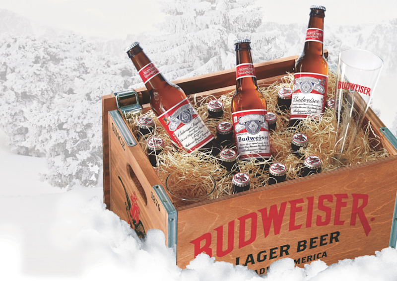 Bottles of Budweiser beer inside a crate that also has a few glasses.