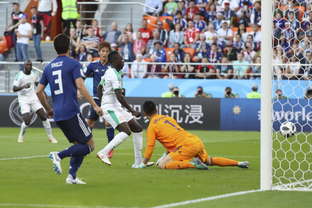 Senegal's Sadio Mane, center, scores his side's opening goal past Japan goalkeeper Eiji Kawashima, right, during the group H match between Japan and Senegal at the 2018 soccer World Cup at the Yekaterinburg Arena in Yekaterinburg , Russia, Sunday, June 24, 2018. (AP Photo/Eugene Hoshiko)