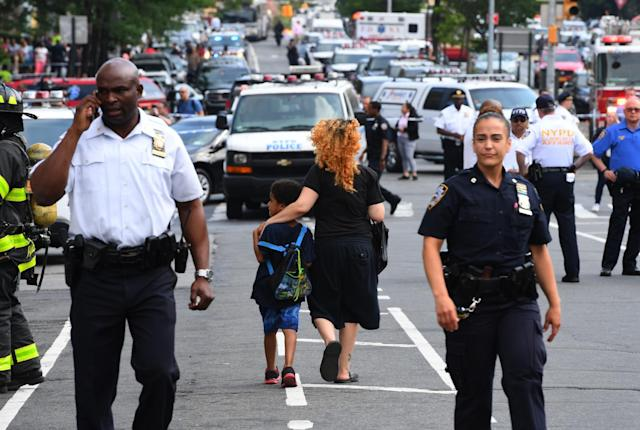 <p>A woman and a child walk past police outside the Bronx-Lebanon Hospital as they respond to an active shooter north of Manhattan in New York on June 30, 2017. (Timothy A. Clary/AFP/Getty Images) </p>