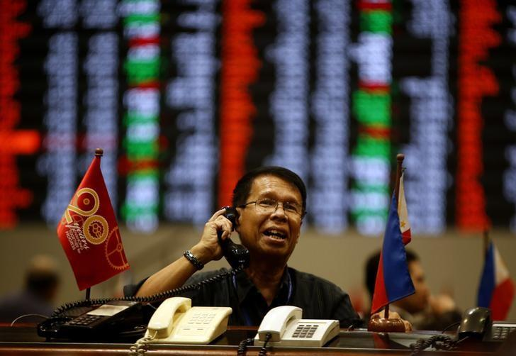 A stock broker takes orders on the telephone during trading at the Philippine Stock Exchange in Manila's Makati financial district