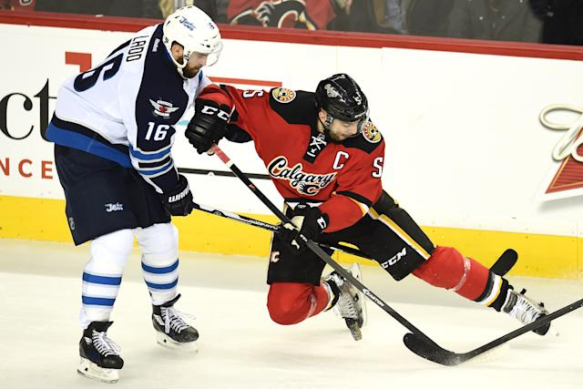 Feb 2, 2015; Calgary, Alberta, CAN; Calgary Flames defenseman Mark Giordano (5) battles for the puck with Winnipeg Jets left wing Andrew Ladd (16) during the second period at Scotiabank Saddledome. (Candice Ward-USA TODAY Sports)