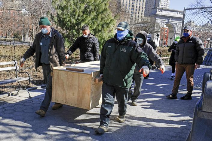In this photo provided by the New York City Parks Department, Green-Wood Cemetery volunteers carry the fragmentary remains of early New Yorkers found during construction in and around Washington Square Park, Tuesday, March 2, 2021, in New York, to be reburied at the site. The human remains were placed in the wooden box and buried five feet below grade within a planting bed in the park, and marked with an engraved paver. (Daniel Avila/New York City Parks Department via AP)