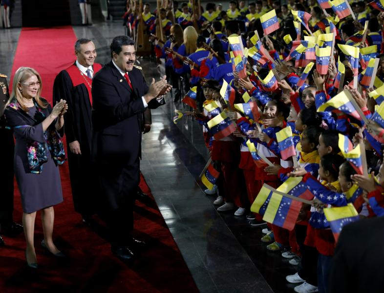 Venezuela's President Nicolas Maduro and first lady Cilia Flores stop to greet flag-waving children upon arrival to the Supreme Court for Maduro's inauguration ceremony in Caracas, Venezuela, Thursday, Jan. 10, 2019. Maduro was sworn in to a second term amid international calls for him to step down and a devastating economic crisis. Behind is Supreme Court President Maikel Moreno. (AP Photo/Ariana Cubillos)
