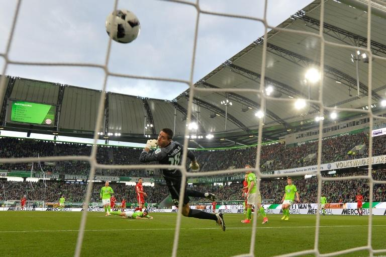 Bayern Munich's Polish forward Robert Lewandowski scores as Wolfsburg's goalkeeper Koen Casteels dives on April 29, 2017 in Wolfsburg, northern Germany