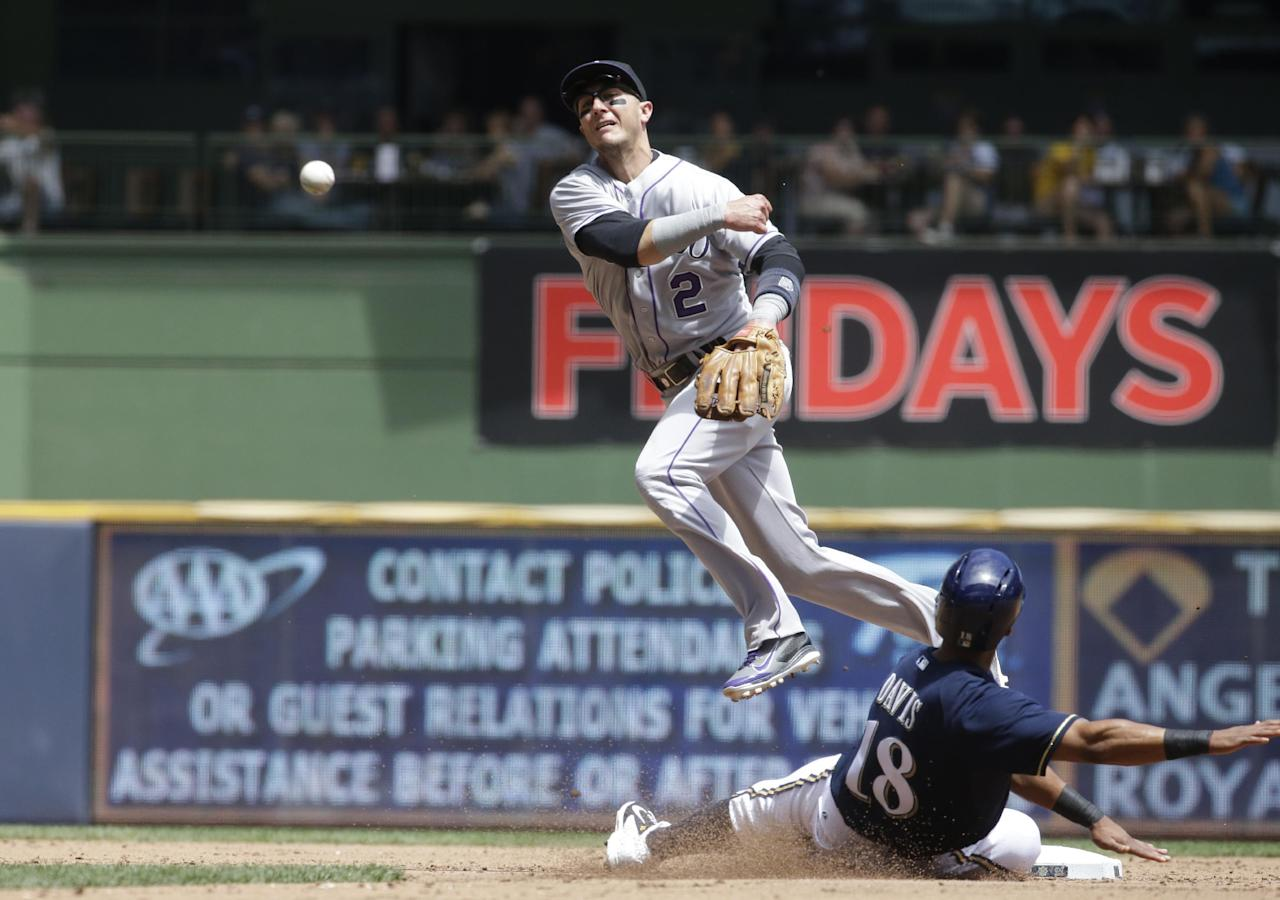 Milwaukee Brewers' Khris Davis is out at second as Colorado Rockies' Troy Tulowitzki turns a double play on a ball hit by Mark Reynolds during the second inning of a baseball game Sunday, June 29, 2014, in Milwaukee. (AP Photo/Morry Gash)