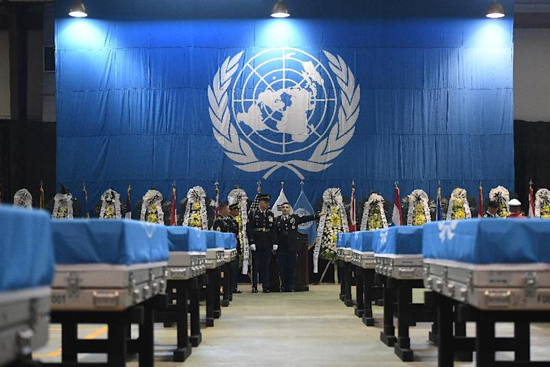 The cases of remains each draped with a white and blue UN flag were lined up in rows as the ceremony got under way