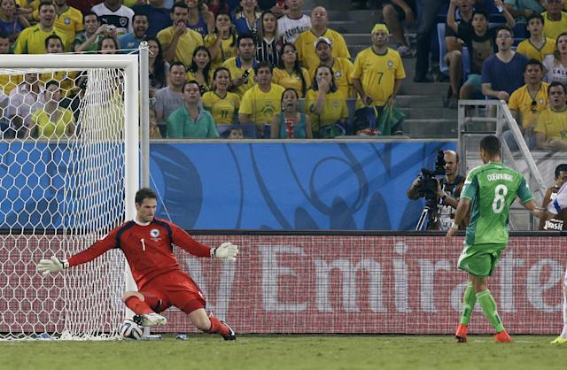 A kick by Nigeria's Peter Odemwingie goes under Bosnia's goalkeeper Asmir Begovic to score Nigeria's first goal during the group F World Cup soccer match between Nigeria and Bosnia at the Arena Pantanal in Cuiaba, Brazil, Saturday, June 21, 2014. (AP Photo/Thanassis Stavrakis)
