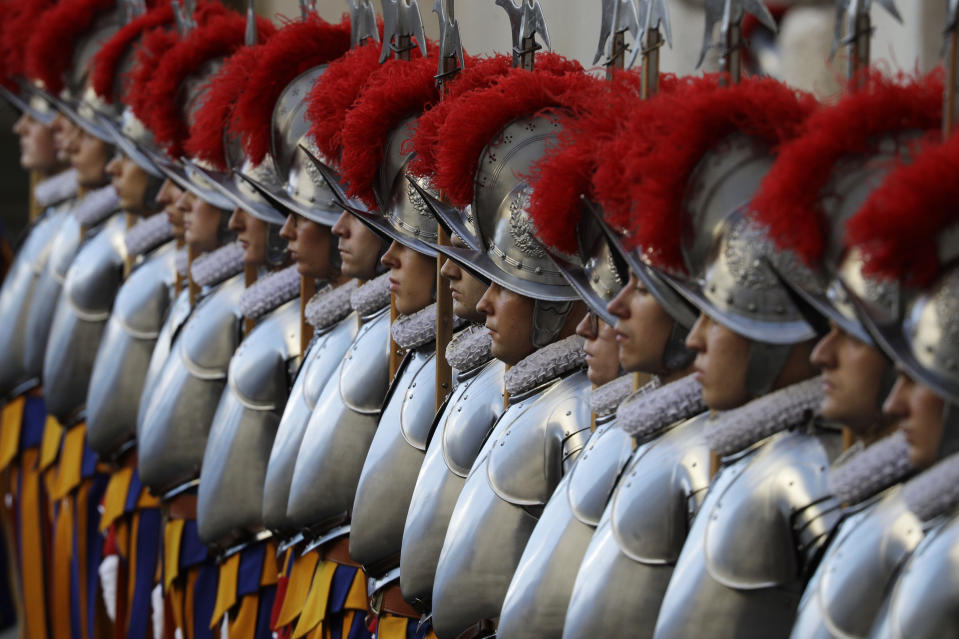 FILE - In this Oct. 4, 2020 file photo, Vatican Swiss Guards stand attention at the St. Damaso courtyard on the occasion of their swearing-in ceremony, at the Vatican, Sunday, Oct. 4, 2020. On Monday, Oct. 12, 2020, the Vatican said in a statement that four Swiss Guards have tested positive for the coronavirus, as the surge in infections in surrounding Italy enters the Vatican walls. (AP Photo/Gregorio Borgia, file)