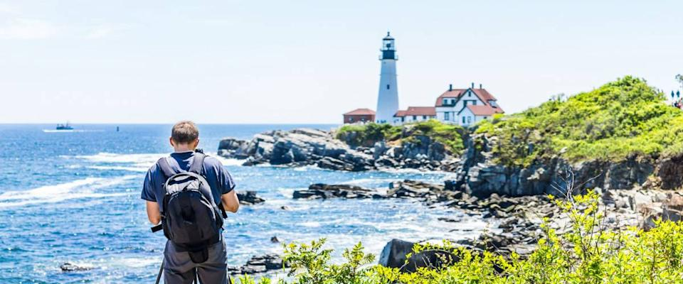 Back of man photographer taking pictures on tripod of Portland Head Lighthouse in Fort Williams park in Maine during summer day