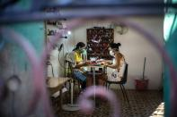 Two women wearing masks as a precaution against the spread of the new coronavirus paint their nails at a home nail salon in Havana, Cuba, Tuesday, March 31, 2020. Cuban authorities are requiring the use of masks for anyone outside their homes. (AP Photo/Ramon Espinosa)